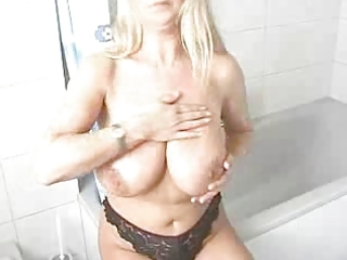 golden-haired milf lathers lotion all over her