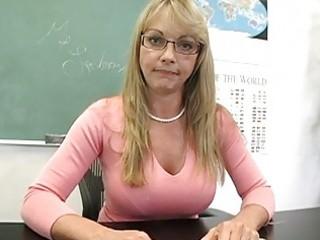 golden-haired older teacher shows off her